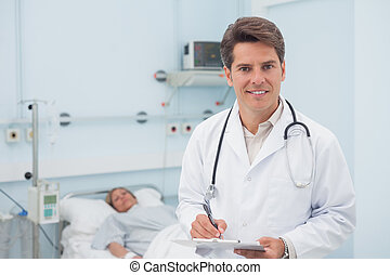 Doctor writing on a chart while smiling in hospital ward