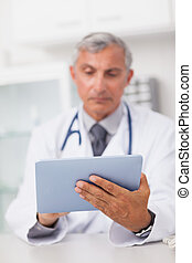 Doctor holding a tablet computer while using it in a medical...