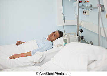 Male patient lying on a medical bed in hospital ward