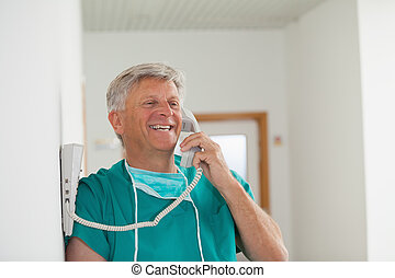 Surgeon smiling while holding a phone in hospital corridor