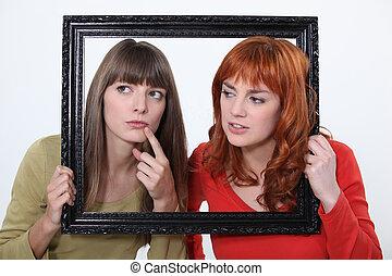 girls behind a wooden frame