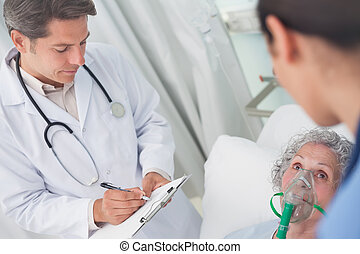 Doctor writing on a clipboard with a pen in hospital ward