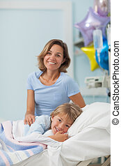 Child lying on a bed next to his mother in hospital ward