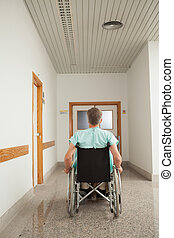 Male patient sitting in a wheelchair in the corridor
