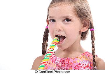 Little girl eating lollipop
