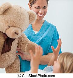 Smiling nurse holding a teddy bear in hospital ward