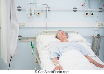 Elderly patient sleeping on a medical bed in hospital ward