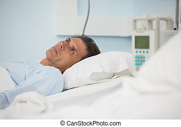 Thoughtful patient lying on a medical bed in hospital ward