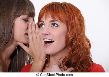Woman whispering into another womans ear