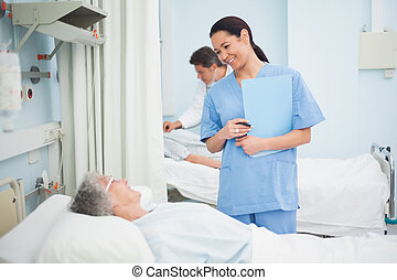 Nurse smiling to a patient in hospital ward
