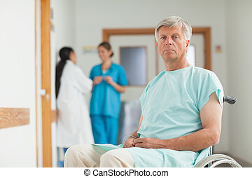 Male patient in a wheelchair looking at camera in hospital...