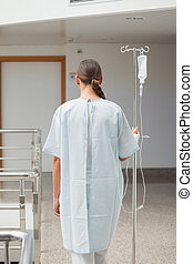 Rear view of a female patient holding a drip stand in...