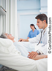 Doctor auscultating a patient with a stethoscope in hospital...