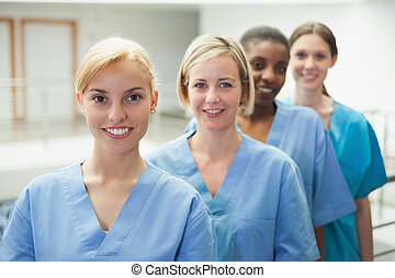 Female nurse looking at camera in hospital hallway