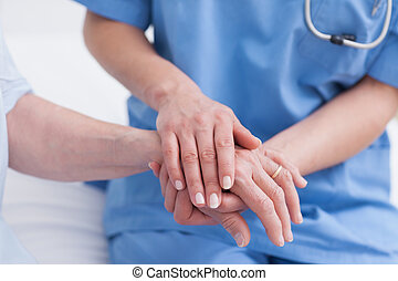 Close up of a nurse touching hand of a patient in hospital...