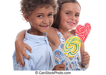 Two friendly kids eating colorful lollipops