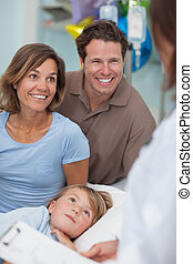 Parents and child looking at a doctor in hospital ward