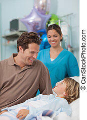 Child lying on a medical bed looking at his father