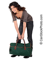 Woman lifting heavy bag