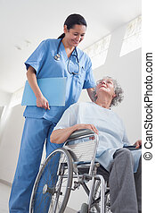 Elderly patient in a wheelchair next to a nurse in hospital...