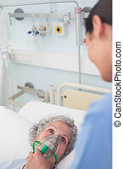 Patient having an oxygen mask on her face in hospital ward