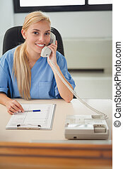 Blonde nurse holding a phone in hospital reception