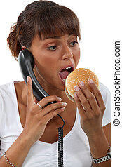 Woman eating a hamburger while talking on the phone
