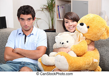 Young couple with teddy bears on a sofa