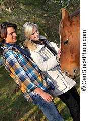 Couple standing by a horse