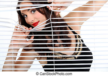 Brunette looking through blinds
