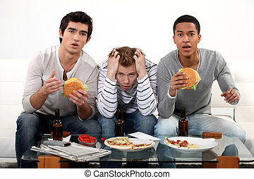 Three male friends eating burgers and watching television
