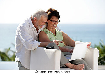 Couple using laptop whilst at holiday resort