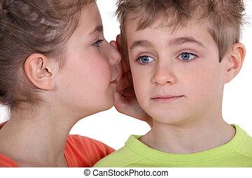 little girl whispering secret to little boy's ear