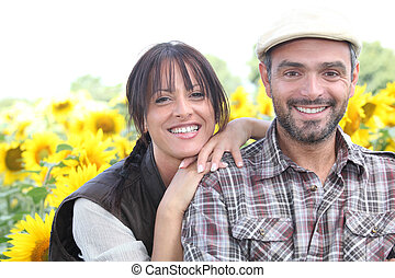 Smiling man and woman in a field of sunflowers