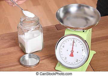 Measuring flour into kitchen scales