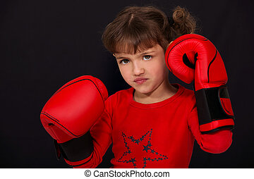 Little girl wearing boxing gloves