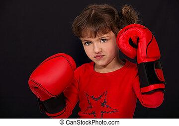 Little girl wearing boxing gloves