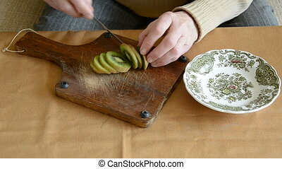 woman hands cutting kiwi fruit - old woman hands cutting...