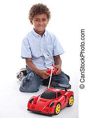 a boy playing with a radio control car
