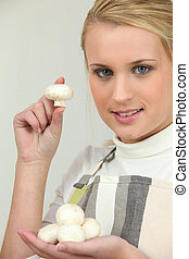 Young woman with a handful of button mushrooms
