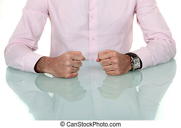Man resting fists on glass table