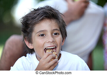 Little boy eating cereal bar outdoors