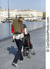 Woman with a pushchair and baby carrier