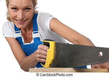 Woman sawing wood