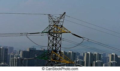 High-voltage wire tower in urban city,wind tree,distant...