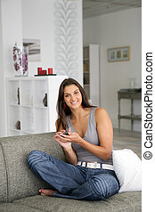 Woman sending text message whilst sat on sofa