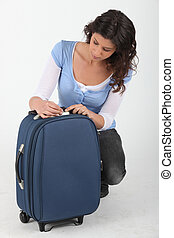 Woman unlocking a suitcase