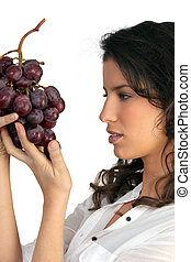 Brunette holding bunch of grapes