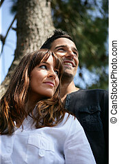 Couple in front of a tree trunk