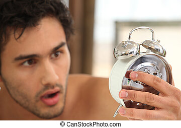 young man looking stunned at alarm clock